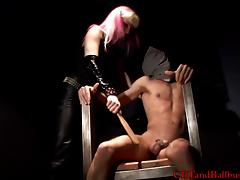 Female captor with pink hair abuses naked prisoner's cock