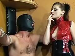 Hawt femdom goddess in red costume burns thrall with smokin' cigarette in dungeon